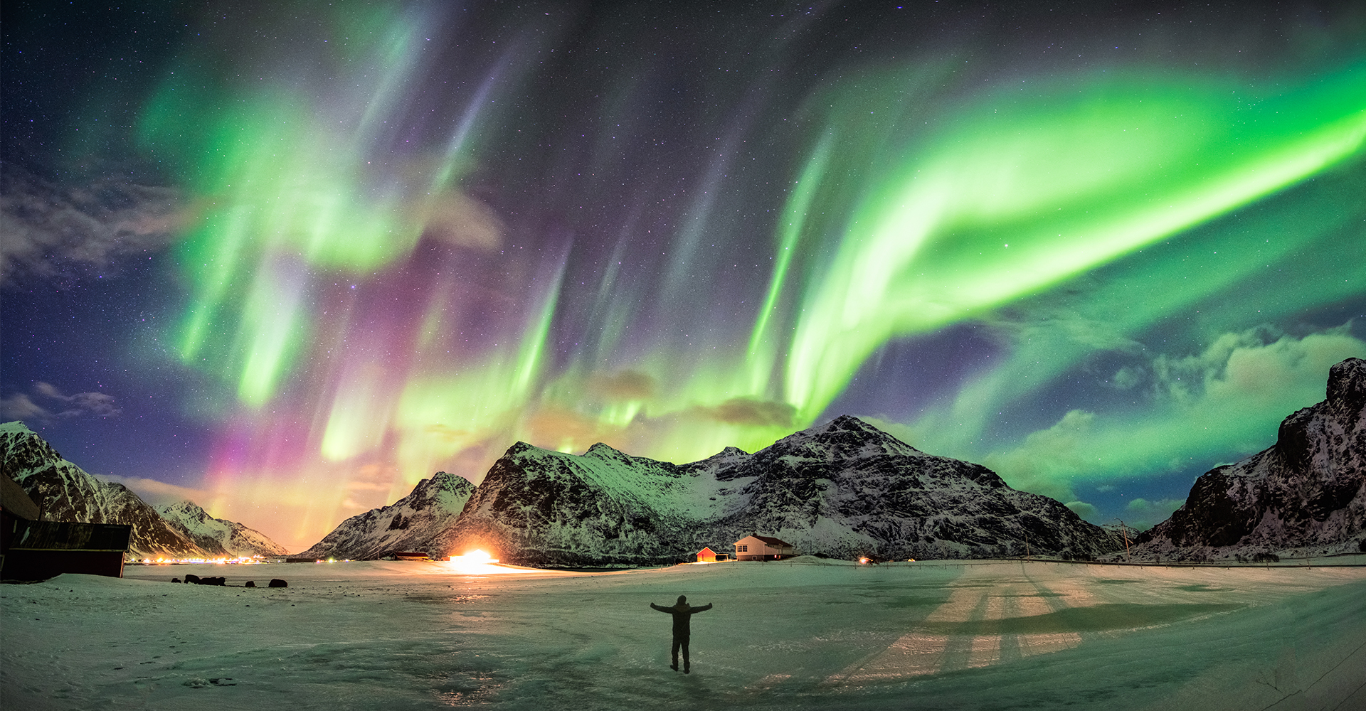 A person standing at night looking up at the Northern Lights