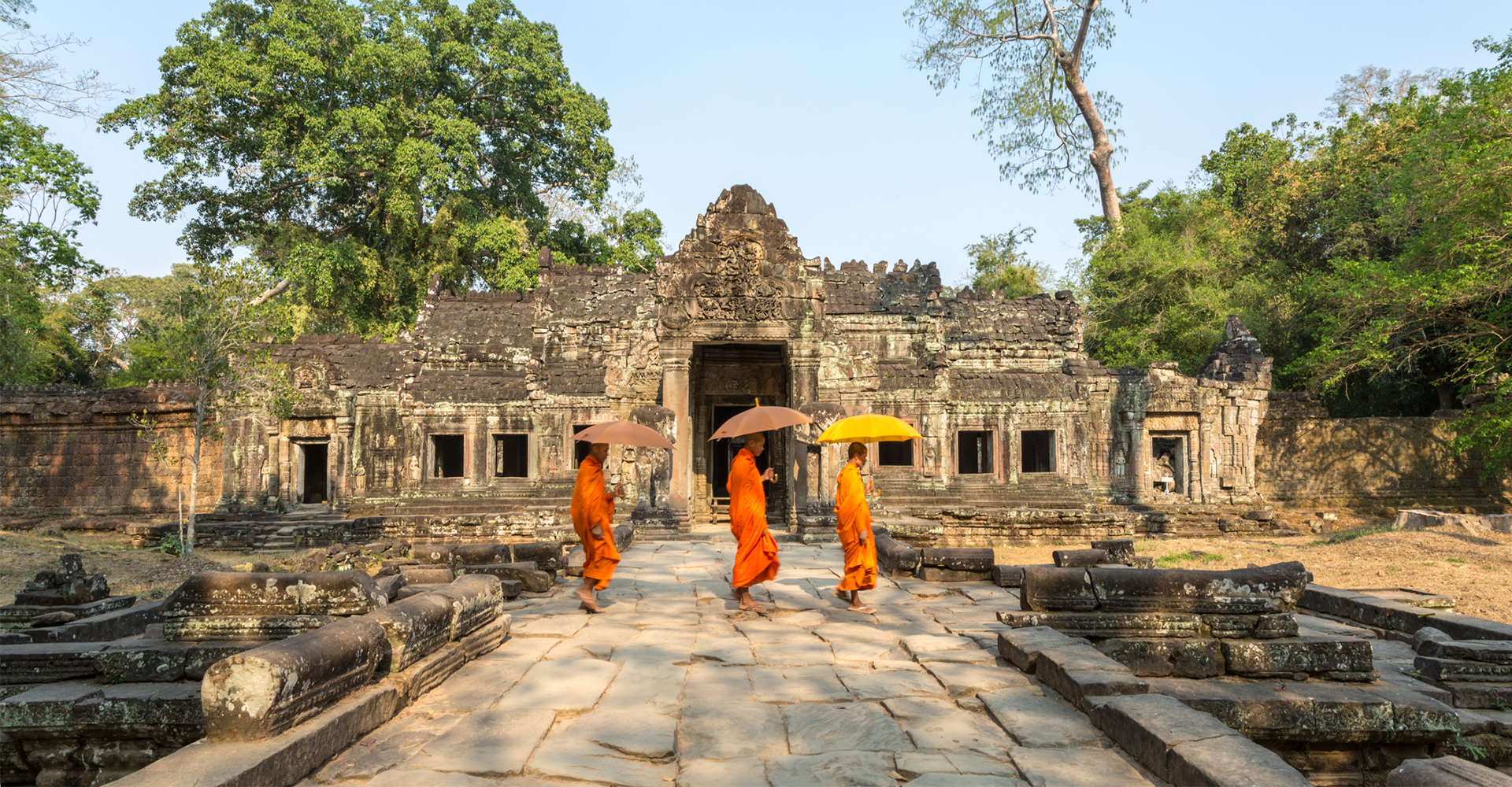 Three monks with umbrellas walking across Preah Khan Temple in Siem Reap, in Cambodia