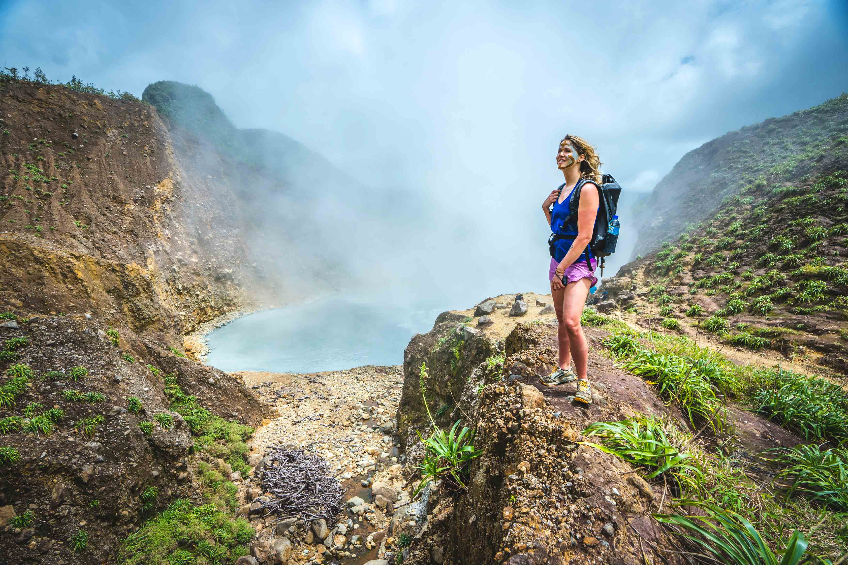 Lady with face paint on looking over a boiling lake in Dominica