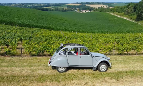 Lois Pryce driving a classic beetle car through a field in France