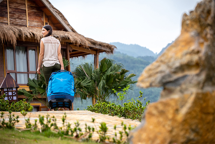 Lady carrying an Osprey duffle suit case to a luxury hut in Asia