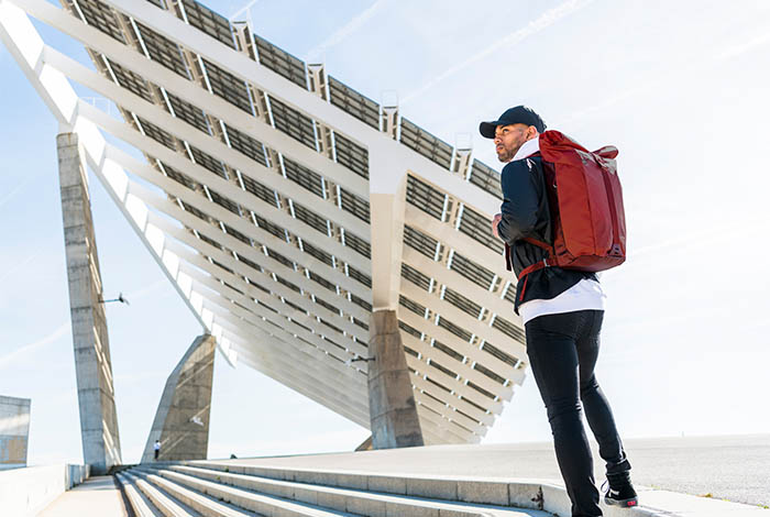 Man in Barcelona looking over his shoulder while carrying an Osprey backpack