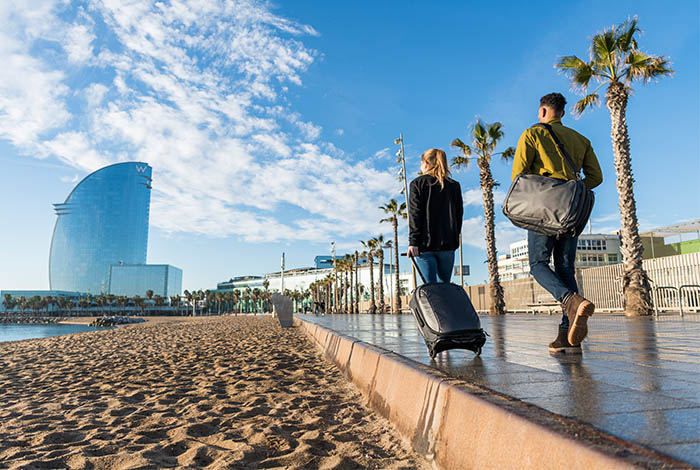 Couple walking next to a beach in Spain carrying their luggage with an Osprey Carry on suitcase