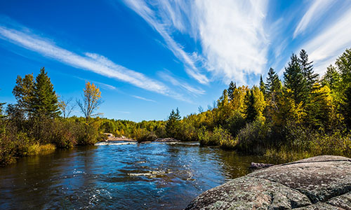 "Tranquil landscape in the Old Pinawa Dam Park. Thin cirrus clouds and foam on the Winnipeg River. Trend of travel ""Around the World"""