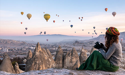 Young girl is shooting photos of hot air balloons flying in red and rose valley in Goreme in Cappadocia in Turkey