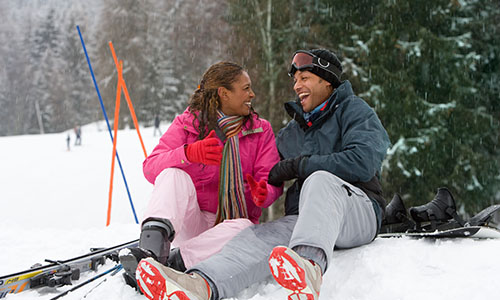 couple sitting in snow on ski vacation